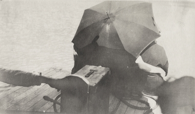 An image of three persons sitting on a dock and holding an umbrella over their heads. This print was found pasted to the back of page 116 of