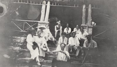A group portrait of men and women, including Margaret Ingels, sitting on stone steps. This print was found pasted to the back of page 113 of