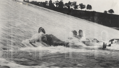 An image of three persons laying in a waterfall. This print was found pasted to the front of page 113 of