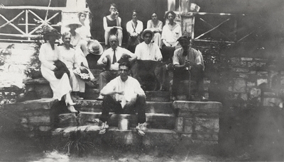 A group portrait of men and women, including Margaret Ingels, sitting on stone steps. This print was found pasted to the back of page 112 of