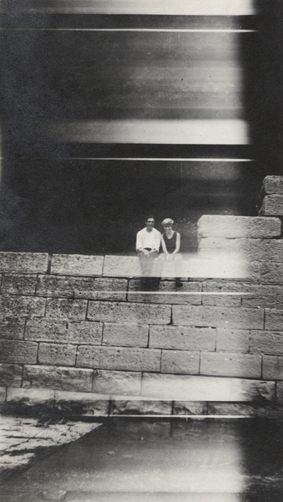 A portrait of an unidentified man and woman sitting on a stone wall. This print was found pasted to the back of page 112 of