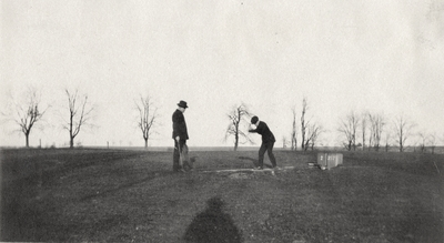 An image of two unidentified men golfing. This print was found pasted to the front of page 115 of