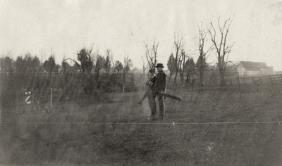 An image of two unidentified men carrying golf bags. This print was found pasted to the back of page 114 of
