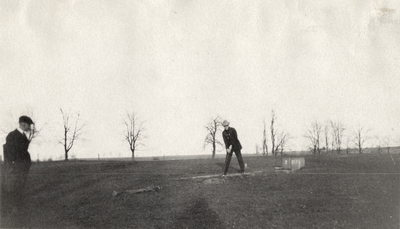 An image of two unidentified men golfing on a golf course. This print was found pasted to the back of page 114 of