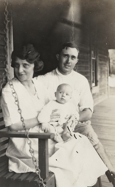 A portrait of an unidentified man, woman and baby on a porch swing. This print has a note on the back. This print was found pasted to the back of page 115 of
