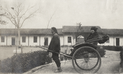 An image of a rickshaw driver with an unidentified woman sitting in a rickshaw. This print was found pasted to the back of page 115 of