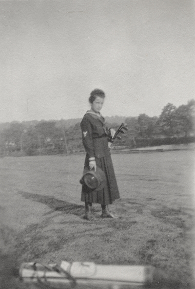 A portrait of Margaret Ingels holding golf clubs in a field. This print was found pasted to the front of page 110 of