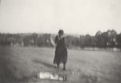 A portrait of Margaret Ingels swinging a golf club. This print was found pasted to the back of page 107 of