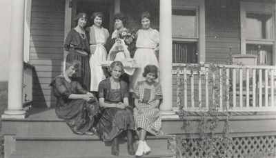 A group portrait of unidentified women sitting and standing on a porch. This print was printed by the Elizabeth Novelty Co. 923 Elizabeth, N. J. This print was found among the