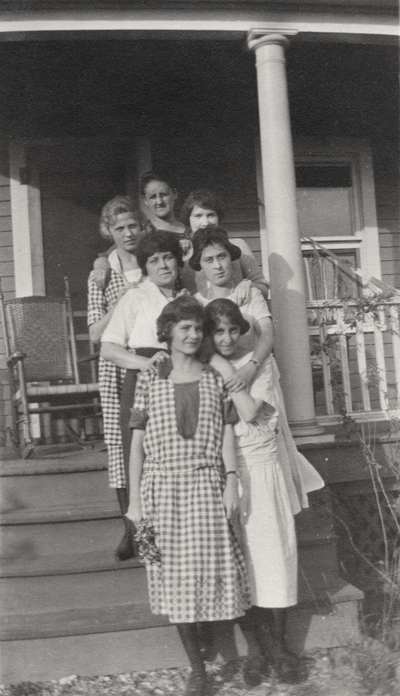 A group portrait of unidentified women standing on the steps leading to a porch. This print was printed by the Elizabeth Novelty Co. 923 Elizabeth, N. J. This print was found among the