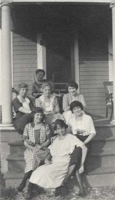 A group portrait of unidentified women sitting on the steps leading to a porch. This print was printed by the Elizabeth Novelty Co. 923 Elizabeth, N. J. This print was found among the