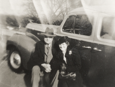 A portrait of an unidentified woman and man sitting on the floor board of a car. The car may be a 1938 Ford four door Sedan