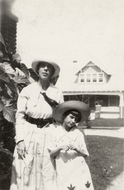 A portrait of a woman (possibly Kate Amanda Ingels Peak) with a girl. A house is in the background. This print was found pasted to the back of page 109 of