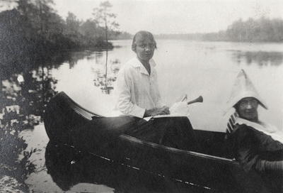 A portrait of two women in a canoe and writing on the print that says,