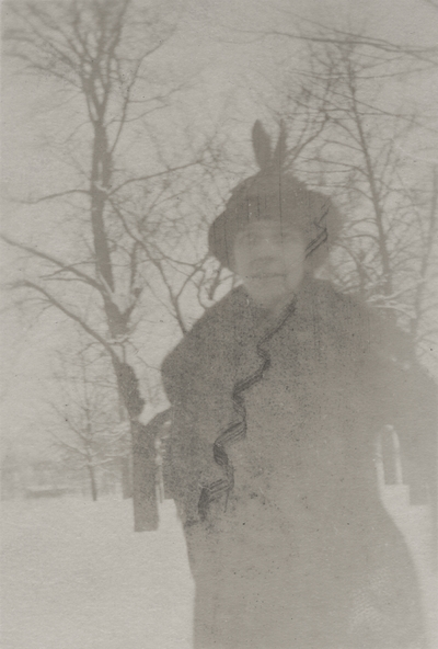 A portrait of an unidentified woman standing outside in snow. This print was found in the pages of