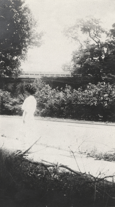 An image of an unidentified woman wearing a hat walking on a sidewalk. This print was found pasted to the front of page 104 of