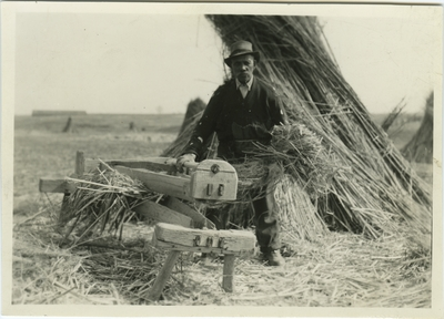 Unknown African American male with a hand brake in a field of hemp stalk stacks at at a Castleton Farm, Lexington, Kentucky; used as illustration facing page 35 in Coleman's