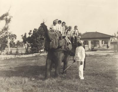 Five children on the back of an elephant and five more children riding in a cart behind the elephant