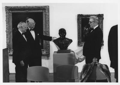 Armand Hammer, left, Bill Sturgill, second from left, and James Stewart, right, are unveiling the bust of Armand Hammer at the opening of the Armand Hammer exhibit in the Art Museum in the Singletary Center; James Stewart is the sculptor and Bill Sturgill was chairman of the University of Kentucky Board of Trustees