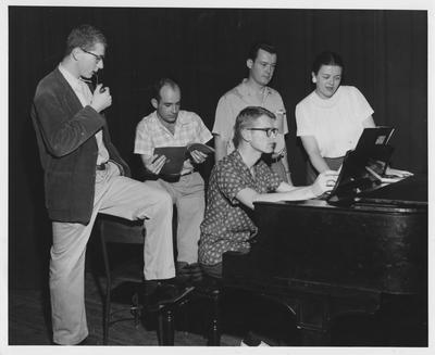 Professor of Voice James King stands, second from right, next to Phyllis Jenness, with others, around a piano