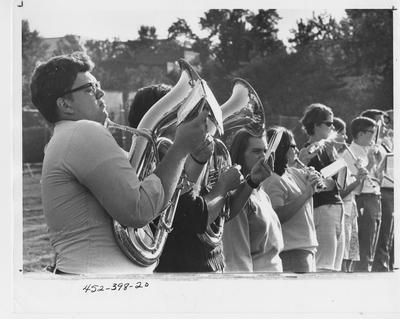 Marching band members hold sheet music while playing their instruments during a University of Kentucky band practice; This image is on page 198 of the 1969 Kentuckian