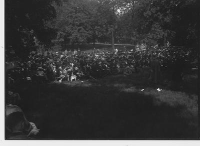 An audience watches an outdoors performance
