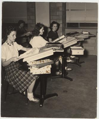 From left to right: Marion Vallean, Evelyn Kennedy, and Mary Edwin Stamper in the Costume Designing Lab; This image is on page 64 of the 1941 Kentuckian