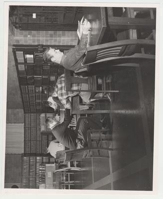 Students studying in the Law Library; First table: Jim Prater; From left to right, Second table: John Morgan, George Shadoan, and Bill Priest (back to camera)