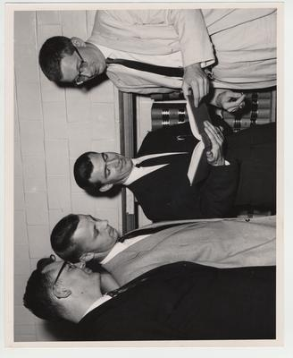 Men look at a book in the Law Library