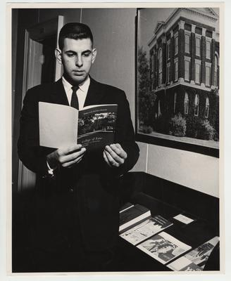 A man reads the College of Law bulletin for 1959 - 1961 in front of a picture of the Administration Building