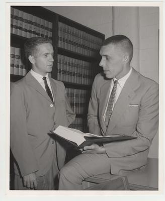 Men holding a book in the Law Library