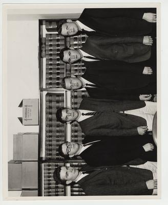 Law students in the Law Library; From left to right: Bill Fortune, Bill Minogue, Joe Savage, Sam Whitehead, and two unidentified men