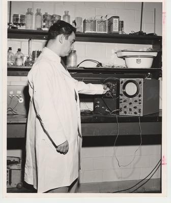 Dr. Louis L. Bojarsky stands in front of nerve testing equipment
