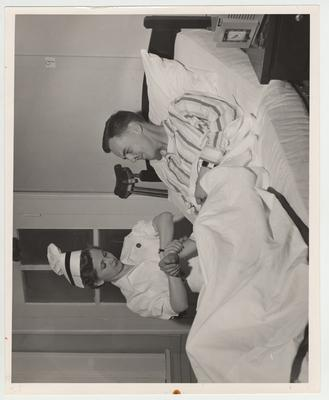 A nurse takes a patient's pulse and temperature in the infirmary