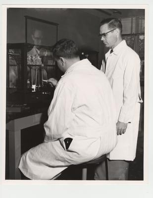 Dr. J. William Miles and Milton H. Nichols in the Pharmacy laboratory