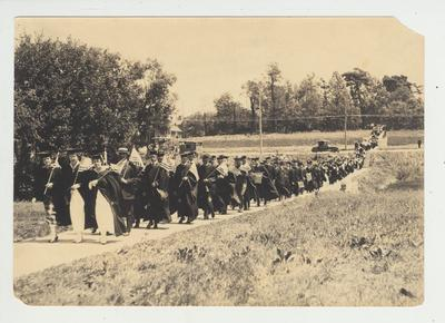 As part of the 1917 commencement, a procession with flags crosses Limestone Street