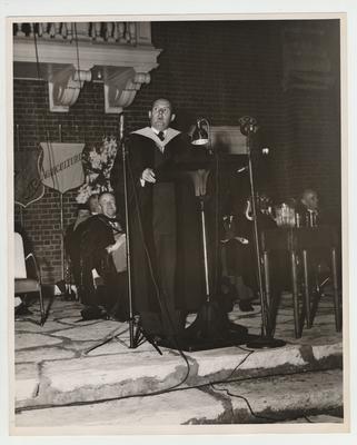 J. D. Williams, a 1925 graduate and President of the University of Mississippi, speaks at commencement; President Donovan is seated in first row, left; Photographer: W. E. Sutherland