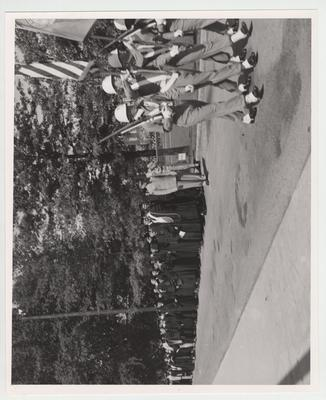 Procession with color guard forms on the driveway by Stoll Field, Frazee Hall in seen in the background