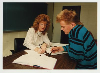 A woman helps a male student in a classroom at Ashland Community College