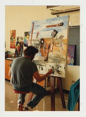 Unidentified male student paints in a classroom at Ashland Community College