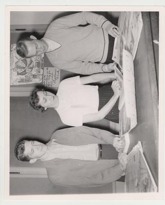 Shirley Hughes (center) flanked by two unidentified men in a Journalism class