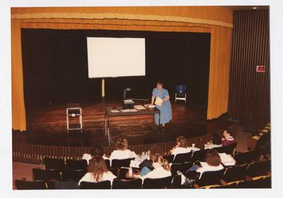 A female professor addresses a class meeting in a theater