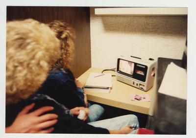 Female students look at an audio visual machine which has visual and a cassette audio tape for class use in the library