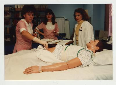 Female students work with a mannequin while an unidentified female professor (right) watches