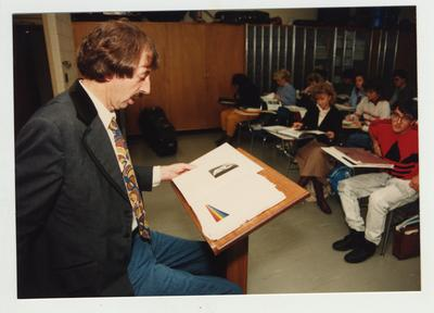 A male professor lectures in front of a classroom as students listen