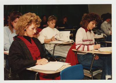 Students listen and take notes during an Art class
