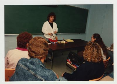 Students listen to a female student giving a presentation