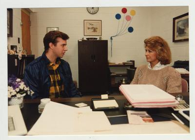 A male student speaks with an unidentified woman in her office