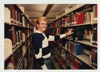 A male student looks for a book in the library