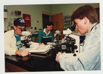 Male students look through microscopes in a laboratory classroom